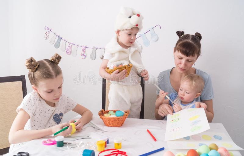 Φεστιβάλ Πάσχας: Η οικογένεια στον πίνακα Το Mom παρουσιάζει τα παιδιά πώς να χρωματίσει τα αυγά Πάσχας στοκ εικόνα