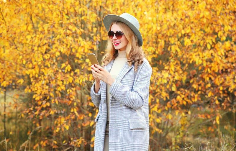 Φθινοπωρινή πορτρέτα, κομψά χαρούμενη χαμογελαστή γυναίκα που κρατά τηλέφωνο φορώντας γκρι παλτό, στρογγυλό καπέλο σε κίτρινα φύλ στοκ εικόνα
