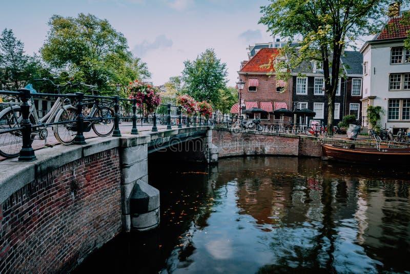 Φθινοπωρινή σκηνή καναλιών του Άμστερνταμ με τα ποδήλατα και τη γέφυρα στοκ εικόνα με δικαίωμα ελεύθερης χρήσης