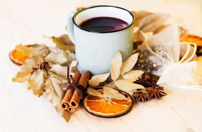 Φθινόπωρο, φύλλα πτώσης, καυτό βράζοντας στον ατμό φλυτζάνι glint του κρασιού στοκ εικόνες