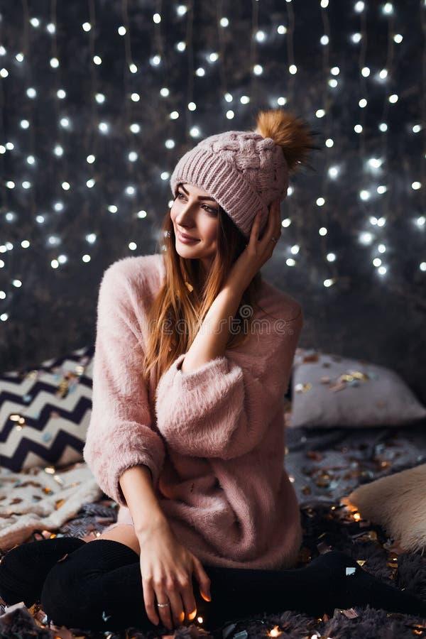 Φθινόπωρο, χειμερινό πορτρέτο: Η νέα χαμογελώντας γυναίκα έντυσε σε μια θερμά μάλλινα ζακέτα και ένα καπέλο που θέτουν μέσα στοκ φωτογραφία με δικαίωμα ελεύθερης χρήσης