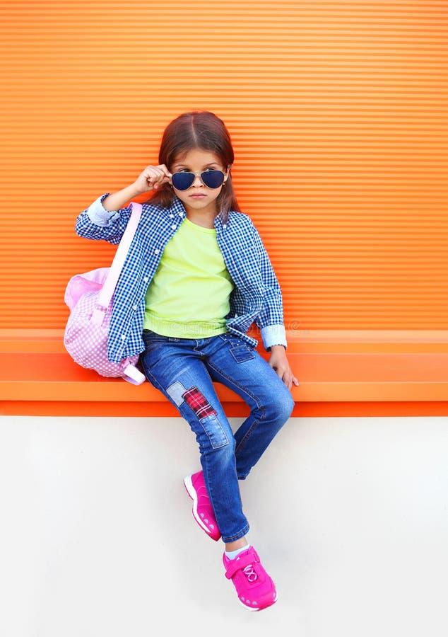 Φθορά παιδιών μικρών κοριτσιών μόδας γυαλιά ηλίου, πουκάμισο, τζιν και σακίδιο πλάτης πέρα από το ζωηρόχρωμο πορτοκάλι στοκ φωτογραφίες