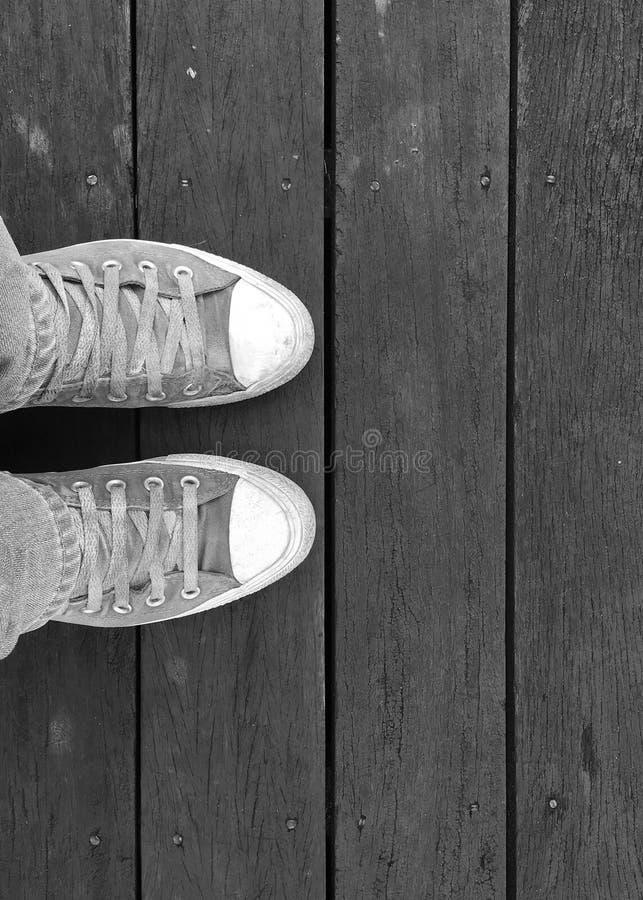 Φθορά των παλαιών πάνινων παπουτσιών, που στέκονται στο ξύλινο floo στοκ φωτογραφίες