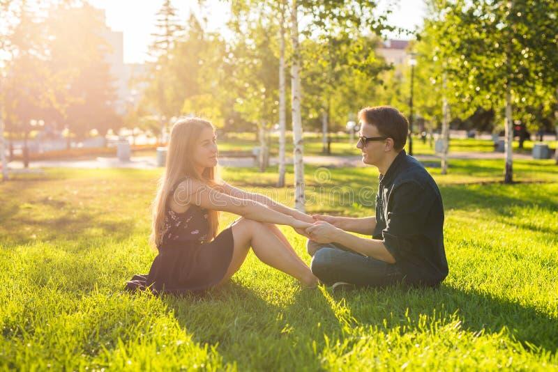 Φιλία, ελεύθερος χρόνος, καλοκαίρι και έννοια ανθρώπων - νέα χαλάρωση ζευγών σε ένα λιβάδι στοκ φωτογραφία με δικαίωμα ελεύθερης χρήσης