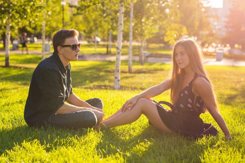 Φιλία, ελεύθερος χρόνος, καλοκαίρι και έννοια ανθρώπων - νέα χαλάρωση ζευγών σε ένα λιβάδι στοκ εικόνες