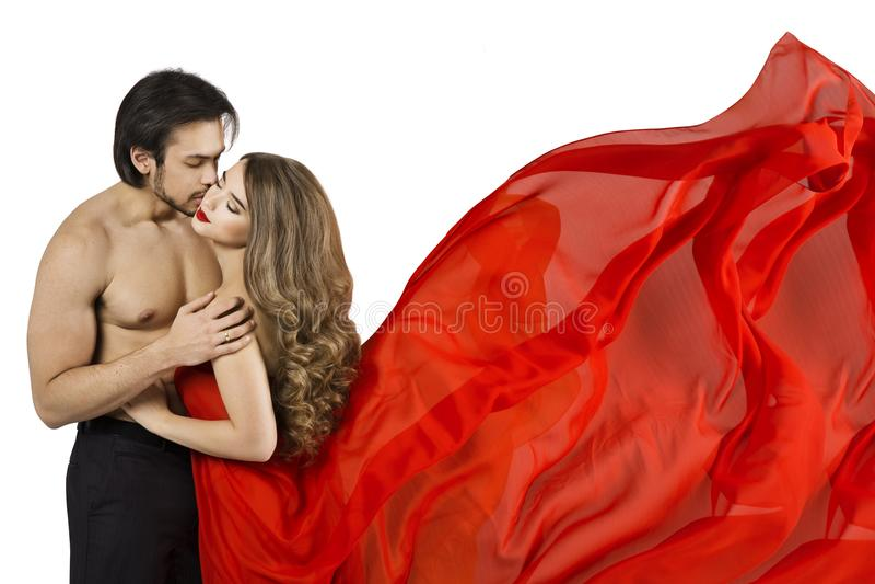 Φιλί ζεύγους, προκλητικός άνδρας που φιλά την όμορφη γυναίκα, κορίτσι στο κόκκινο κυματίζοντας φόρεμα στοκ εικόνες