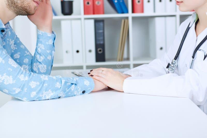 Φιλικά θηλυκά χέρια γιατρών ` s που κρατούν το αρσενικό υπομονετικό χέρι ` s για την ενθάρρυνση και το ενσυναίσθημα Εμπιστοσύνη σ στοκ φωτογραφία