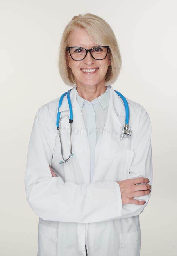 Φιλική ανώτερη γυναίκα γιατρός χαμογελά. Απομονωμένο στοκ εικόνα