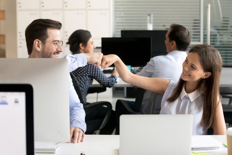 Φιλική πρόσκρουση πυγμών συναδέλφων χαμόγελου στον εργασιακό χώρο στοκ φωτογραφία με δικαίωμα ελεύθερης χρήσης