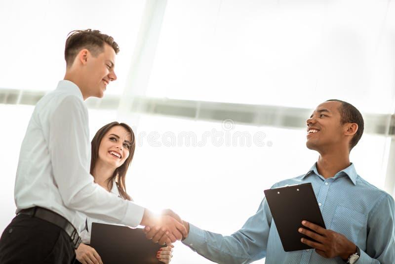 Φιλικοί επιχειρηματίες που τινάζουν τα χέρια στο θολωμένο υπόβαθρο στοκ εικόνες