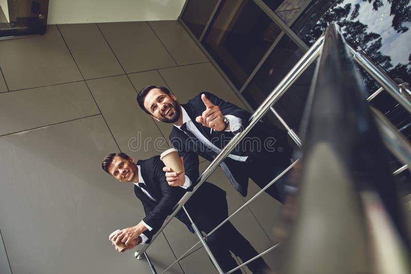 Φιλικοί συνάδελφοι που κοιτούν από απόσταση ενώ πίνουν καφέ σε εξωτερι στοκ φωτογραφίες