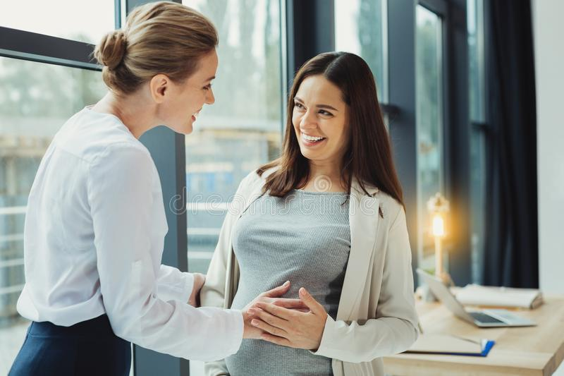 Φιλικός γραμματέας σχετικά με την κοιλιά του έγκυων συναδέλφου και του χαμόγελού της στοκ φωτογραφίες