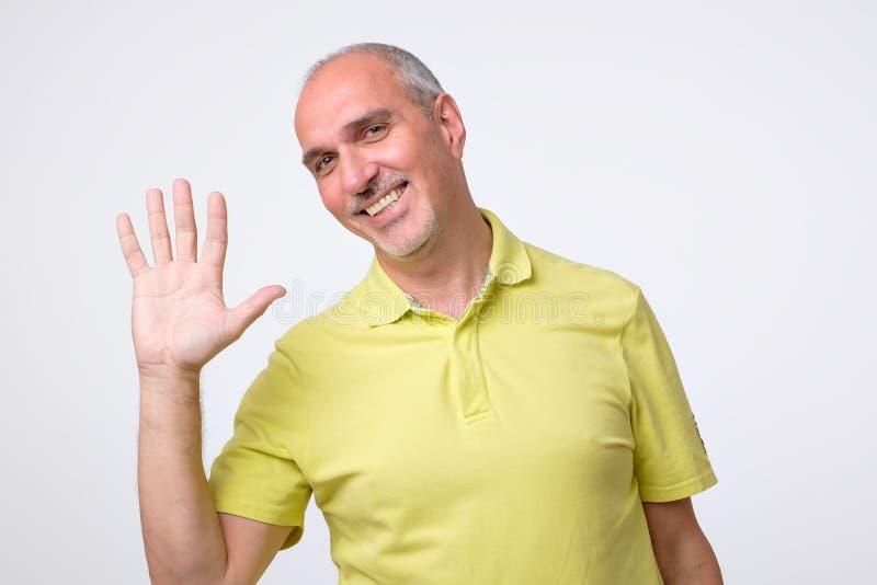 Φιλικός-κοιτάζοντας ελκυστικό ευρωπαϊκό να παραμερίσει ατόμων παραδώστε γειά σου τη χειρονομία χαμογελώντας χαρωπά στοκ εικόνα