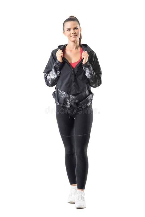 Φιλικός χαμογελώντας την αρκετά φίλαθλη γυναίκα στο σακάκι φορμών γυμναστικής που θέτει και που εξετάζει τη κάμερα στοκ φωτογραφία