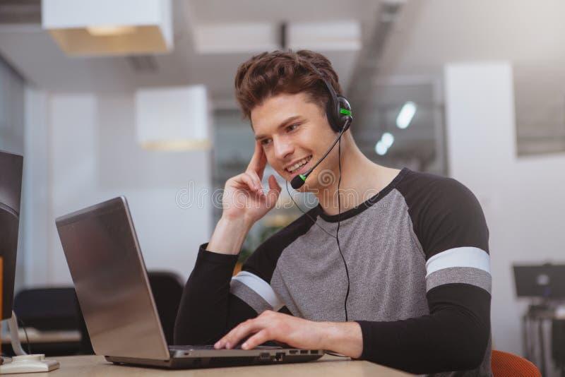 Φιλικός χειριστής υποστήριξης πελατών με την κάσκα που λειτουργεί στο τηλεφωνικό κέντρο στοκ φωτογραφίες με δικαίωμα ελεύθερης χρήσης