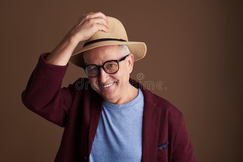 Φιλικό άτομο που χαμογελά βάζοντας στο καπέλο αχύρου του στοκ φωτογραφία