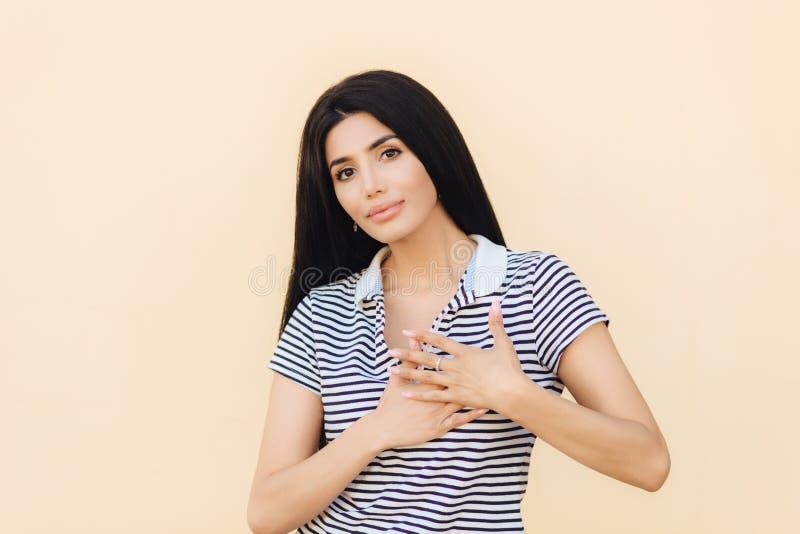 Φιλικό να φανεί θηλυκό brunette κρατά τα χέρια στην καρδιά όπως εκφράζει η ευγνωμοσύνη της, έχει τη σοβαρή έκφραση, φορά τα περισ στοκ εικόνες με δικαίωμα ελεύθερης χρήσης