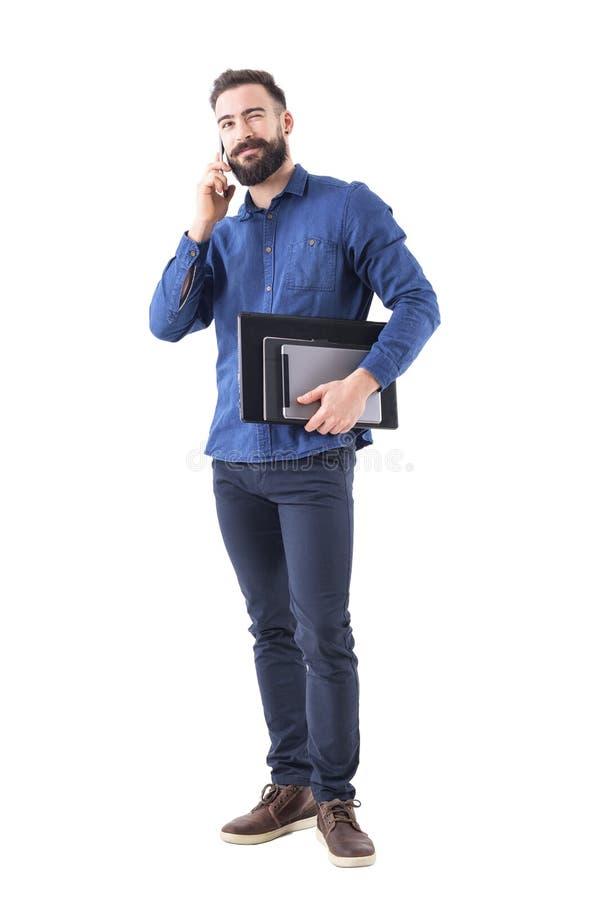 Φιλικό χαλαρωμένο επιτυχές ευτυχές επιχειρησιακό άτομο που μιλά στο τηλέφωνο που κλείνει το μάτι και που ανατρέχει στοκ εικόνες με δικαίωμα ελεύθερης χρήσης