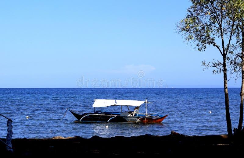 Φιλιππινέζικο αλιευτικό σκάφος που στέκεται στη θάλασσα από την ακτή στοκ εικόνα με δικαίωμα ελεύθερης χρήσης