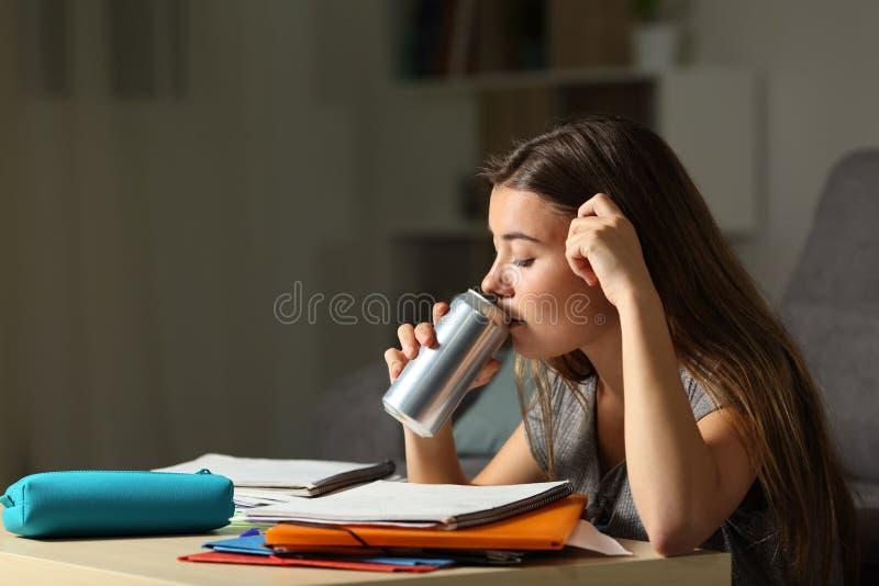Φιλομαθής έφηβος που μελετά το ενεργειακό ποτό κατανάλωσης στοκ φωτογραφία