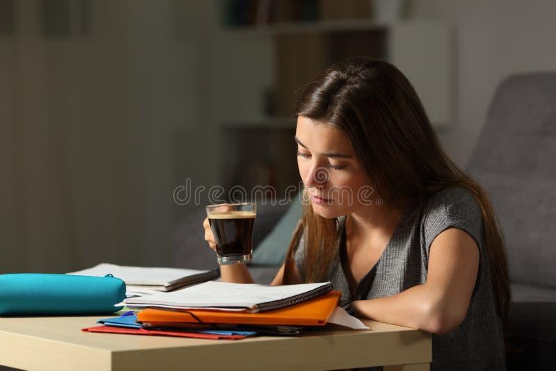 Φιλομαθής σπουδαστής που μελετά κρατώντας ένα φλυτζάνι καφέ στοκ εικόνα με δικαίωμα ελεύθερης χρήσης
