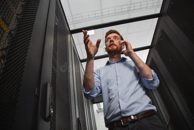 Φιλόδοξος τεχνικός ΤΠ που οργανώνει το ντουλάπι κεντρικών υπολογιστών στοκ εικόνες