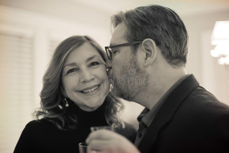 Φιλώντας σύζυγος συζύγων στο μάγουλο στη νέα παραμονή ετών στο σπίτι στοκ εικόνες