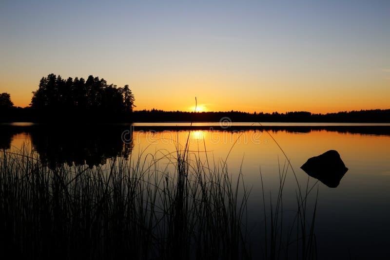 Φινλανδία: Ηλιοβασίλεμα από μια λίμνη στοκ φωτογραφία