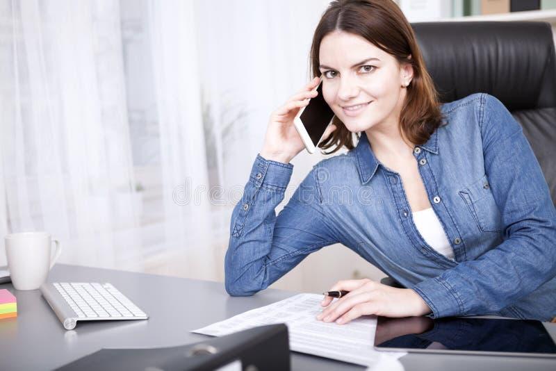 Φιλική επιχειρηματίας που χαμογελά καθώς παίρνει μια κλήση στοκ εικόνες
