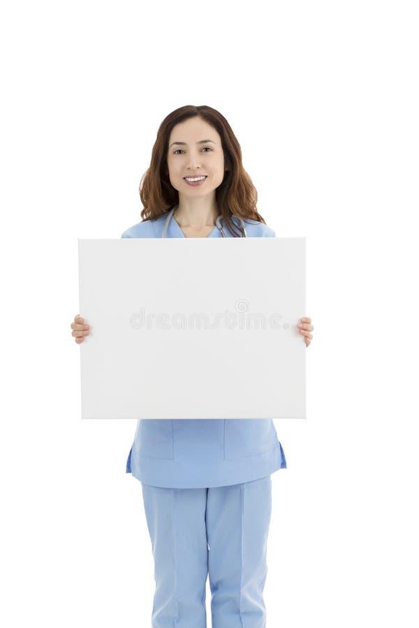 Φιλική καυκάσια γιατρός ή νοσοκόμα θηλυκών που παρουσιάζει άσπρη κενή αφίσα για τη διαφήμιση στοκ φωτογραφία με δικαίωμα ελεύθερης χρήσης