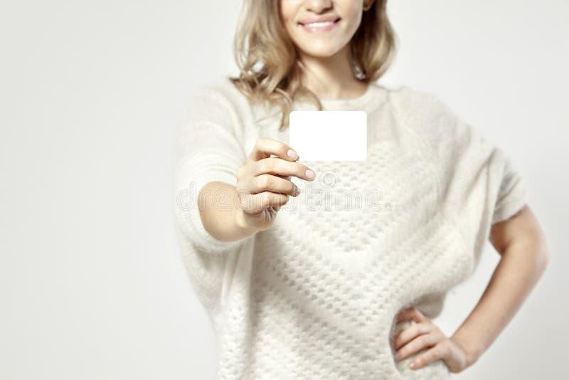 Φιλική όμορφη Ευρωπαία γυναίκα που κρατά μια επαγγελματική κάρτα στοκ φωτογραφία