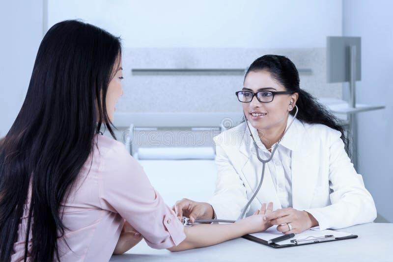 Φιλικός γιατρός που χαμογελά ενώ ακούοντας ο κτύπος της καρδιάς στοκ φωτογραφία με δικαίωμα ελεύθερης χρήσης