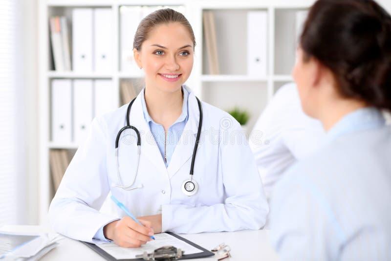 Φιλικός χαμογελώντας γιατρός και υπομονετική συνεδρίαση στον πίνακα Πολύ καλές ειδήσεις και υψηλού επιπέδου έννοια ιατρικής υπηρε στοκ εικόνες