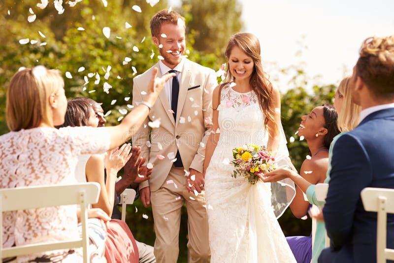 Φιλοξενούμενοι που ρίχνουν το κομφετί πέρα από τη νύφη και το νεόνυμφο στο γάμο στοκ φωτογραφία με δικαίωμα ελεύθερης χρήσης