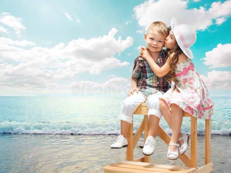 Φιλώντας αγόρι μικρών κοριτσιών στο τοπίο θάλασσας στο ηλιοβασίλεμα στοκ φωτογραφία