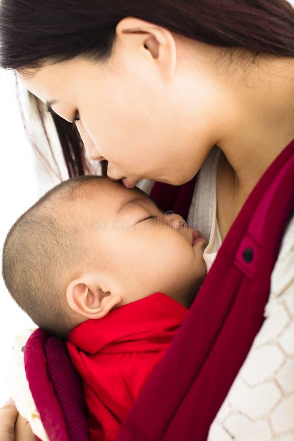 Φιλώντας μωρό μητέρων στο μεταφορέα μωρών στοκ εικόνες