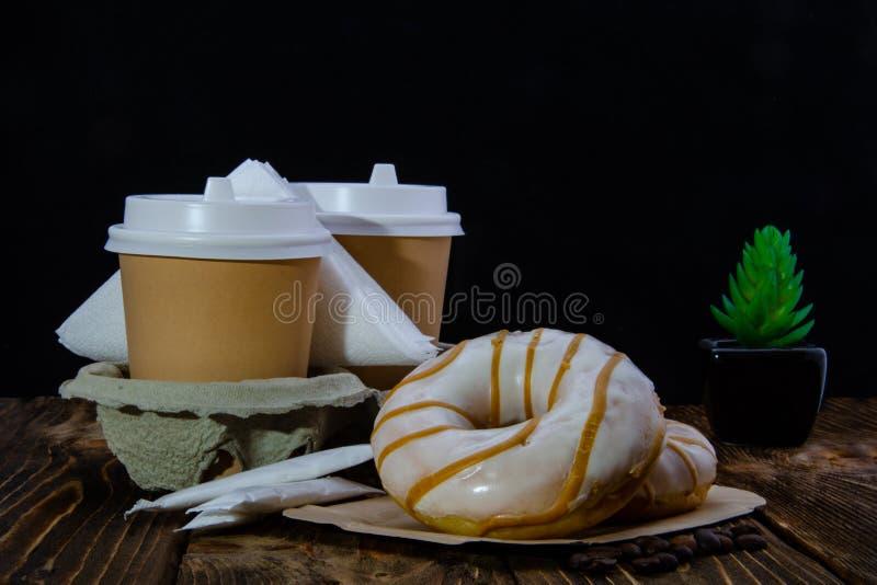 Φλιτζάνια του καφέ εγγράφου, ζάχαρη στις τσάντες, donuts Ξύλινος πίνακας   στοκ εικόνες