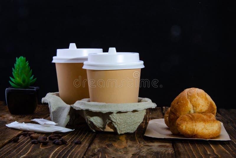 Φλιτζάνια του καφέ εγγράφου, ζάχαρη στις τσάντες, donuts Croissant Ξύλινος πίνακας στοκ φωτογραφία με δικαίωμα ελεύθερης χρήσης