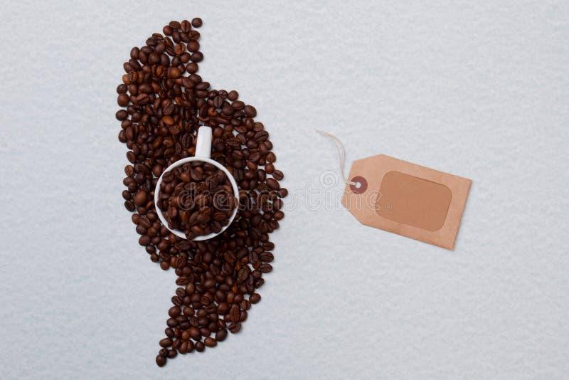 Φλιτζάνι καφέ σε μια στοίβα και λευκή ετικέτα στοκ φωτογραφία