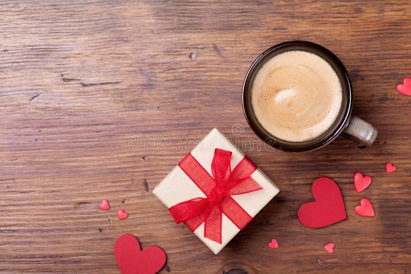 Φλιτζάνι του καφέ, δώρο ή παρούσα κόκκινης καρδιά κιβωτίων και στην αγροτική ξύλινη άποψη επιτραπέζιων κορυφών Πρόγευμα διακοπών  στοκ φωτογραφία με δικαίωμα ελεύθερης χρήσης