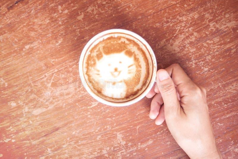 Φλιτζάνι του καφέ εκμετάλλευσης χεριών γυναικών Τοπ όψη Χαριτωμένη τέχνη latte, γάτα στοκ εικόνες με δικαίωμα ελεύθερης χρήσης