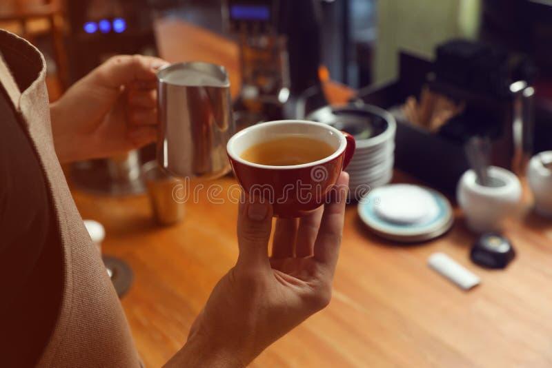 Φλιτζάνι του καφέ και κανάτα εκμετάλλευσης Barista με το γάλα στο μετρητή φραγμών, κινηματογράφηση σε πρώτο πλάνο στοκ εικόνες