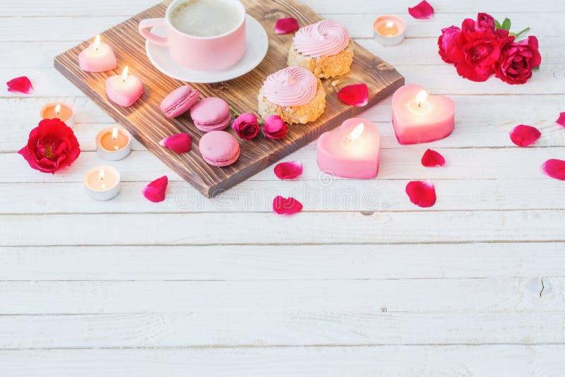 φλιτζάνι του καφέ με τα κέικ, τα κεριά και τα τριαντάφυλλα στο άσπρο υπόβαθρο στοκ εικόνες