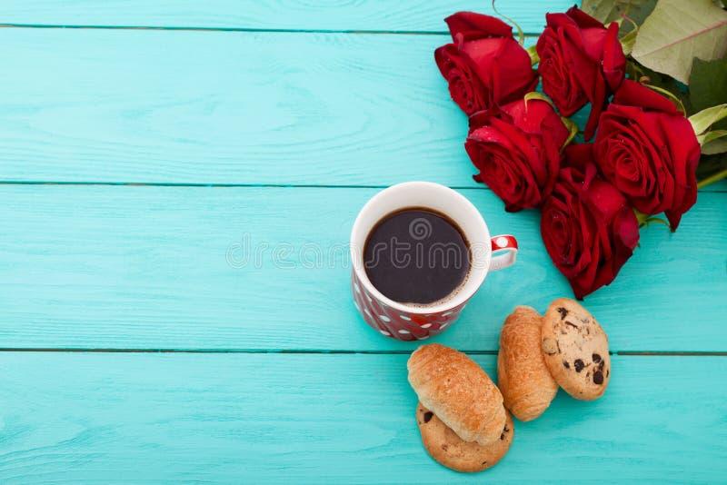Φλιτζάνι του καφέ με τα croissants και τα μπισκότα και κόκκινα τριαντάφυλλα στο μπλε ξύλινο υπόβαθρο διάστημα αντιγράφων Χλεύη επ στοκ φωτογραφίες με δικαίωμα ελεύθερης χρήσης