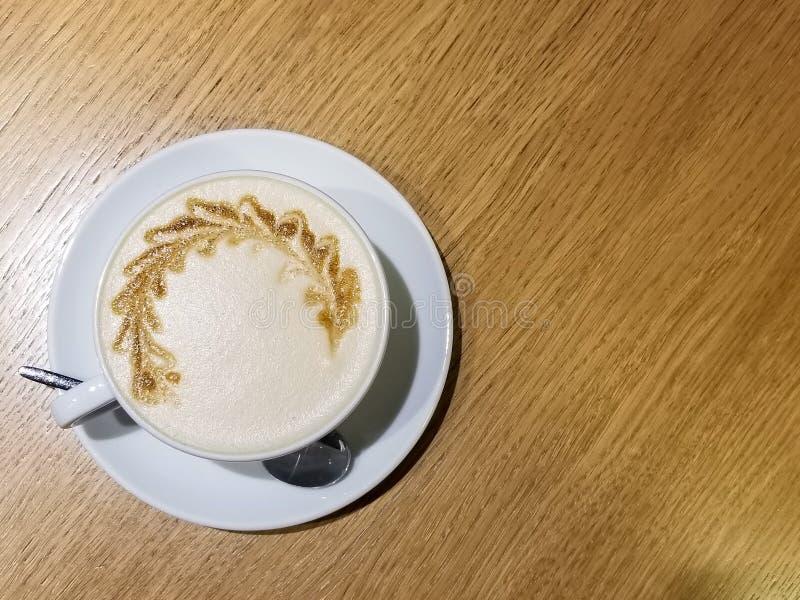 Φλιτζάνι του καφέ με την τέχνη latte ξύλινο επιτραπέζιο στενό σε επάνω στοκ εικόνες