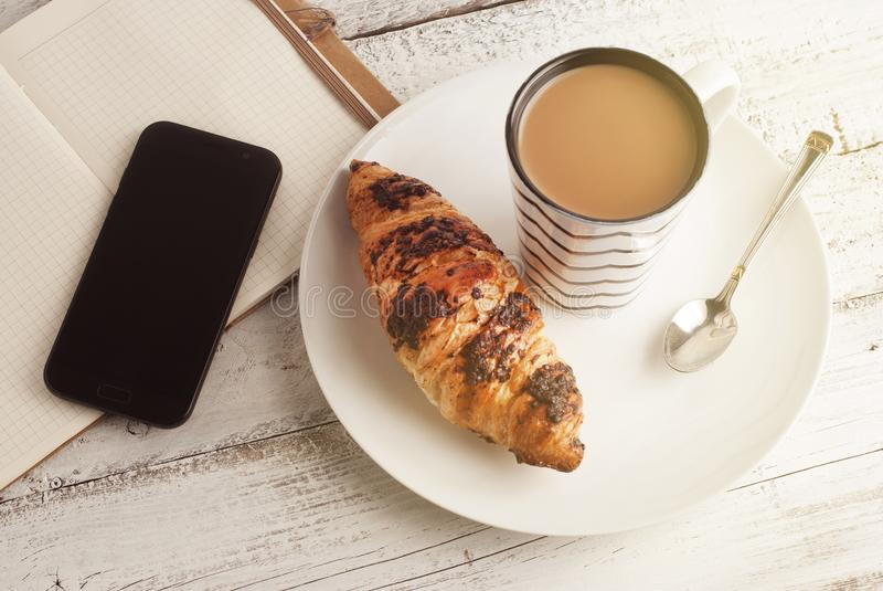 Φλιτζάνι του καφέ με croissant σε ένα άσπρο πιάτο και ένα κινητό τηλέφωνο, ένα smartphone και το σημειωματάριο, πέρα από το άσπρο στοκ εικόνα με δικαίωμα ελεύθερης χρήσης