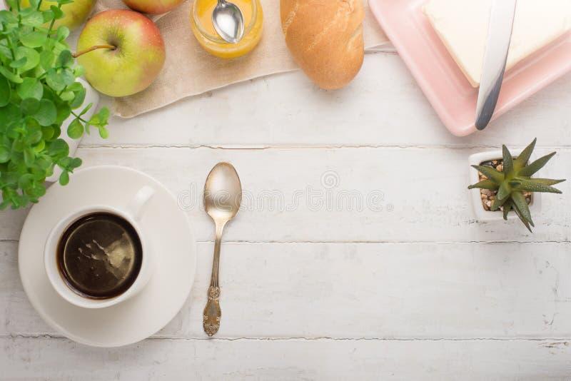 Φλιτζάνι του καφέ, ξυπνητήρι, μήλα, βούτυρο και baguette πρωινού, σε μια ελαφριά κουζίνα Περιοχή υποβάθρου, η έννοια ενός φωτεινο στοκ εικόνα με δικαίωμα ελεύθερης χρήσης