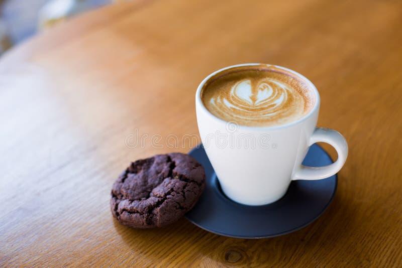 Φλιτζάνι του καφέ που εξυπηρετείται με το μπισκότο σοκολάτας στοκ φωτογραφία με δικαίωμα ελεύθερης χρήσης