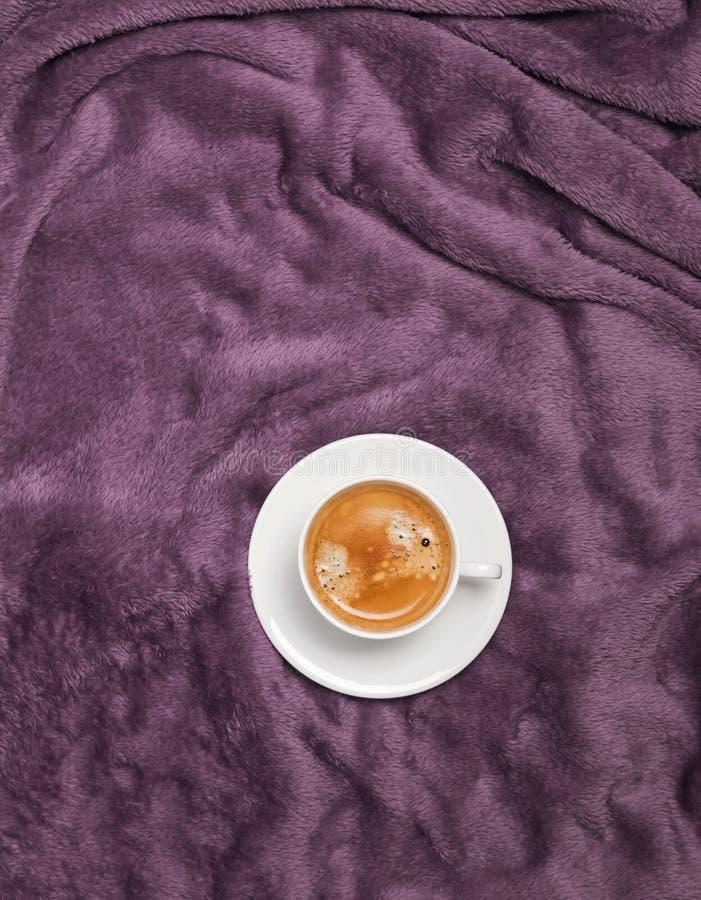 Φλιτζάνι του καφέ στο κρεβάτι με το πορφυρό καρό ή τη γενική, τοπ άποψη στοκ εικόνα