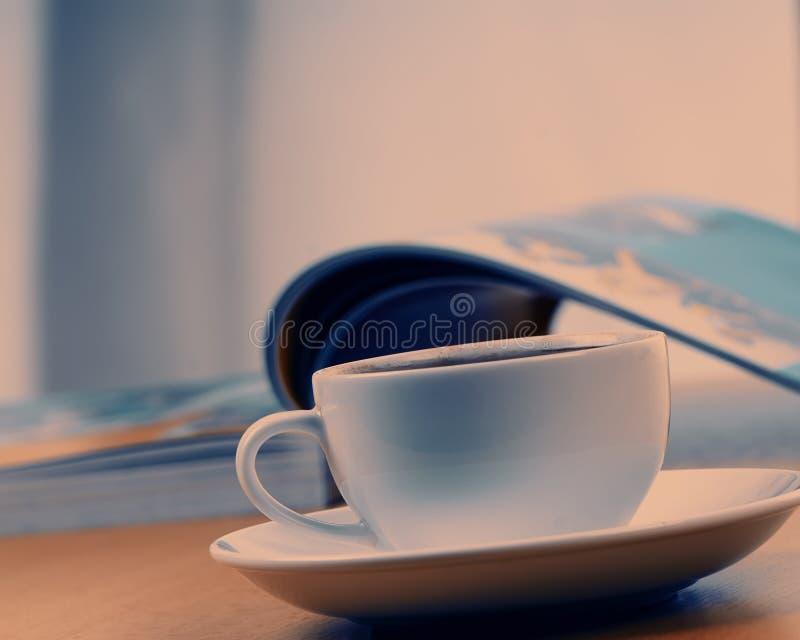 Φλιτζάνι του καφέ στο υπόβαθρο ενός ανοικτού καταλόγου Ένα φλυτζάνι στοκ φωτογραφίες με δικαίωμα ελεύθερης χρήσης